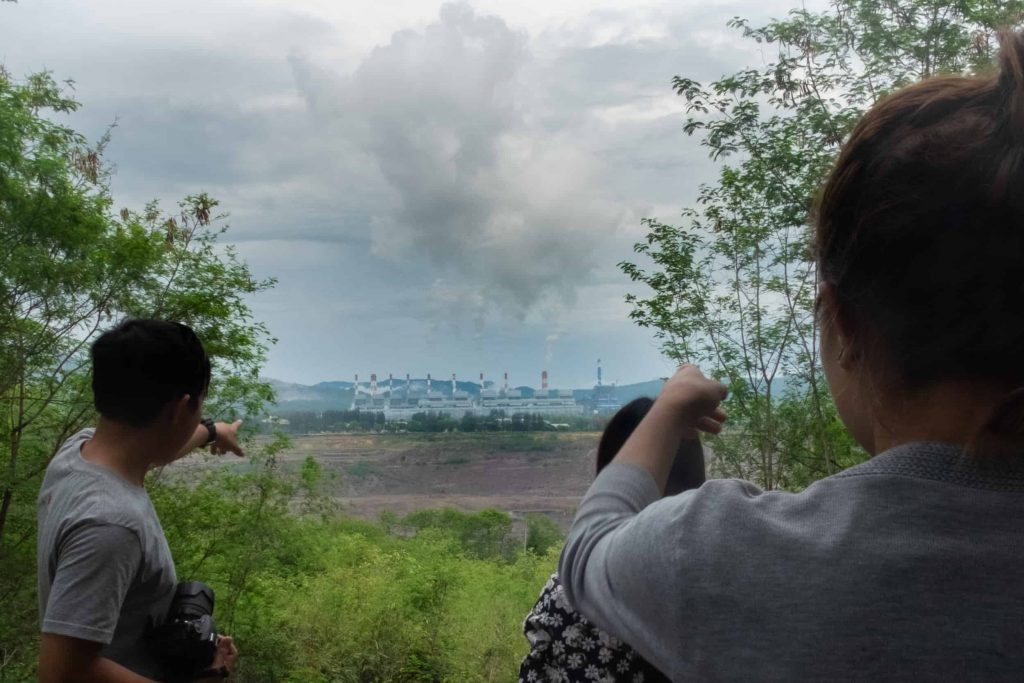 Community members from Nan look out at the Mae Moh open-pit lignite coal mine and power plant.