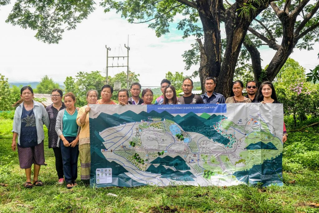 Members of the Mae Moh and Nan communities pose with a map of one of the Nan communities, showing crops, rivers and watersheds.