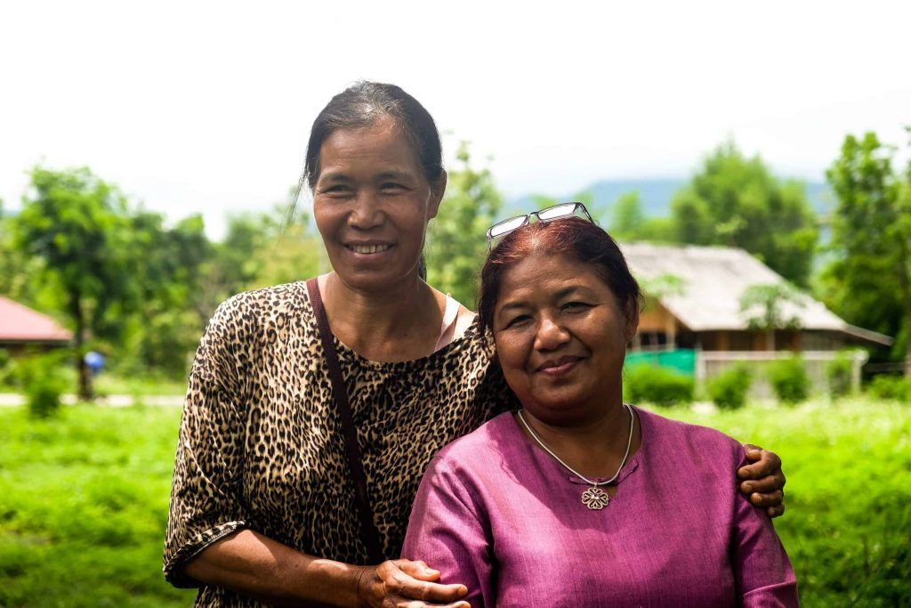 A woman from Nan and a woman from Mae Moh pose after connecting around their shared stories of facing pollution and threats to their local environments.
