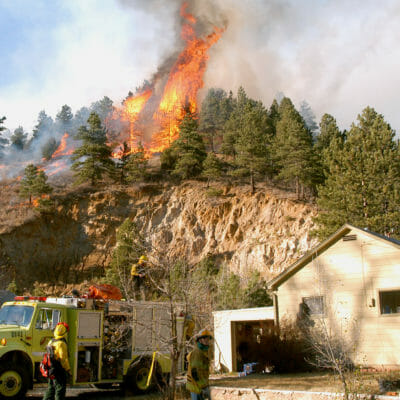 The Overland Fire advances into the town of Jamestown, Colorado, on Wednesday, October 29, 2003. Fire engines were stationed at the homes and buildings to protect the structures from the flames.
