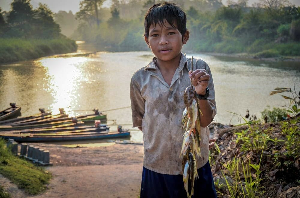 A young Mondul Yorn villagers shows the fish that he caught.