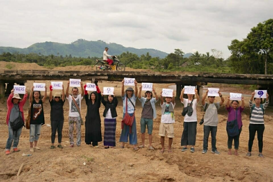 "Supporters of the Dawei communities pose in the dry riverbed of the Myaung Pyo River, asking ""Where has the river gone?"" (In Myanmar language (Burmese), ""Myit bae pyauk twar thar hlae?"")."