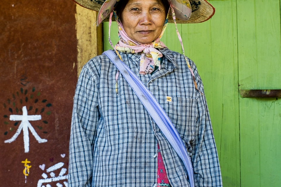 Farmer at Nong Tao Village in front of a traditional house made of mud. The leaders of Nong Tao Village participate in various projects to develop sustainable methods of agriculture and architecture