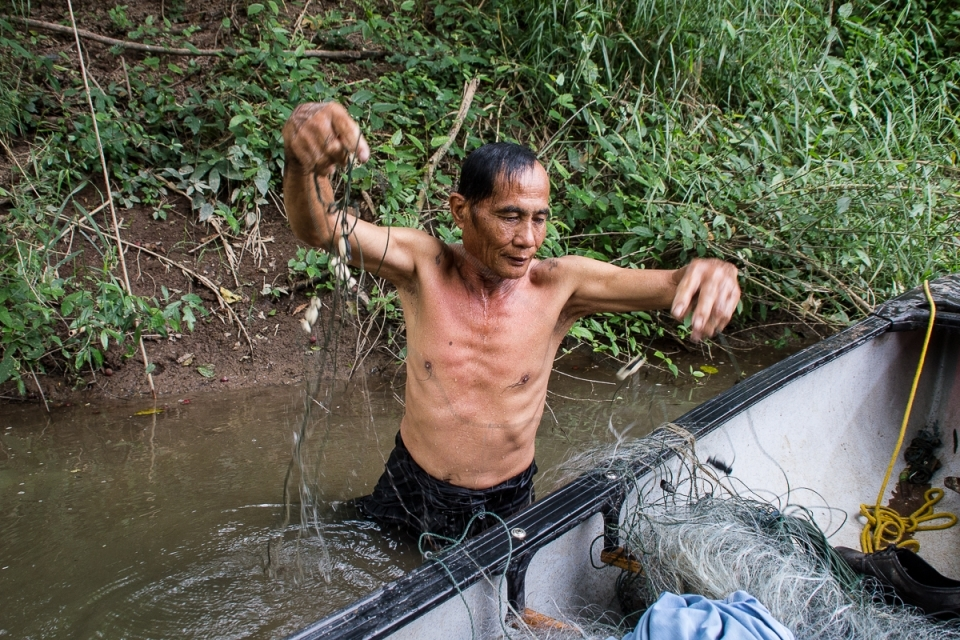 Uncle Nan hauls in his nets and fresh fish catch from the Yom River.