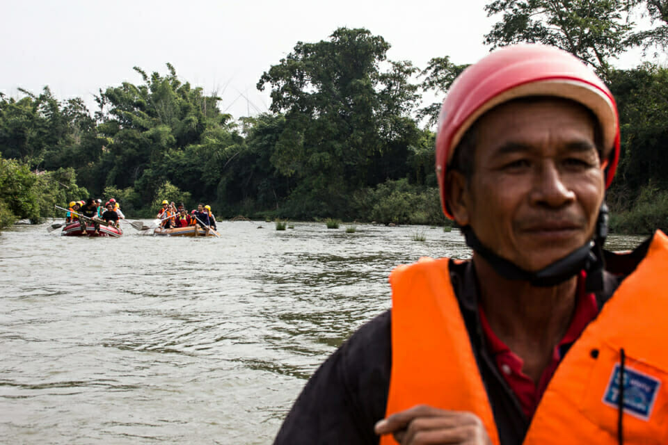 """EarthRights School Mekong students raft down the Yom River with Uncle Kham, assistant fisherman. The community organizes different activities for visitors to understand the values of their natural surroundings. Kaeng Sua Ten means """"The tiger dancing over the rapids."""""""