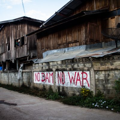 "Graffiti in Sa-iab Village. Every house has signs that say things like ""We will fight and die here."" Kaeng Sua Ten is well known for protesting by making effigies of politicians who support the construction of the dam. It is believed that through a spirit medium they can curse the politicians until they fall ill and die."